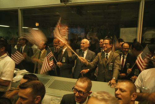 Smiling in relief, men wave flags as they view safe Columbia landing.