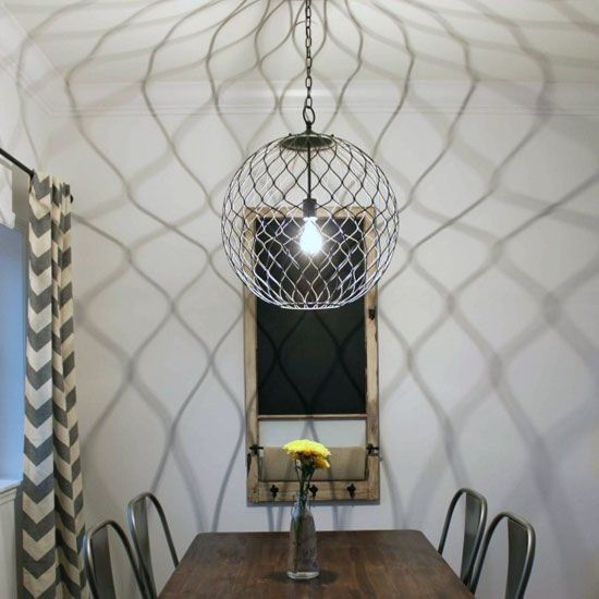 A Modern Urban Dining Room With Showpiece Sphere Lighting Fixture And Re Purposed Window
