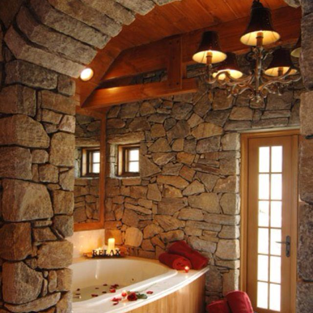 Romantic/cozy bathroom. I can't get over the light, stonework and tub.