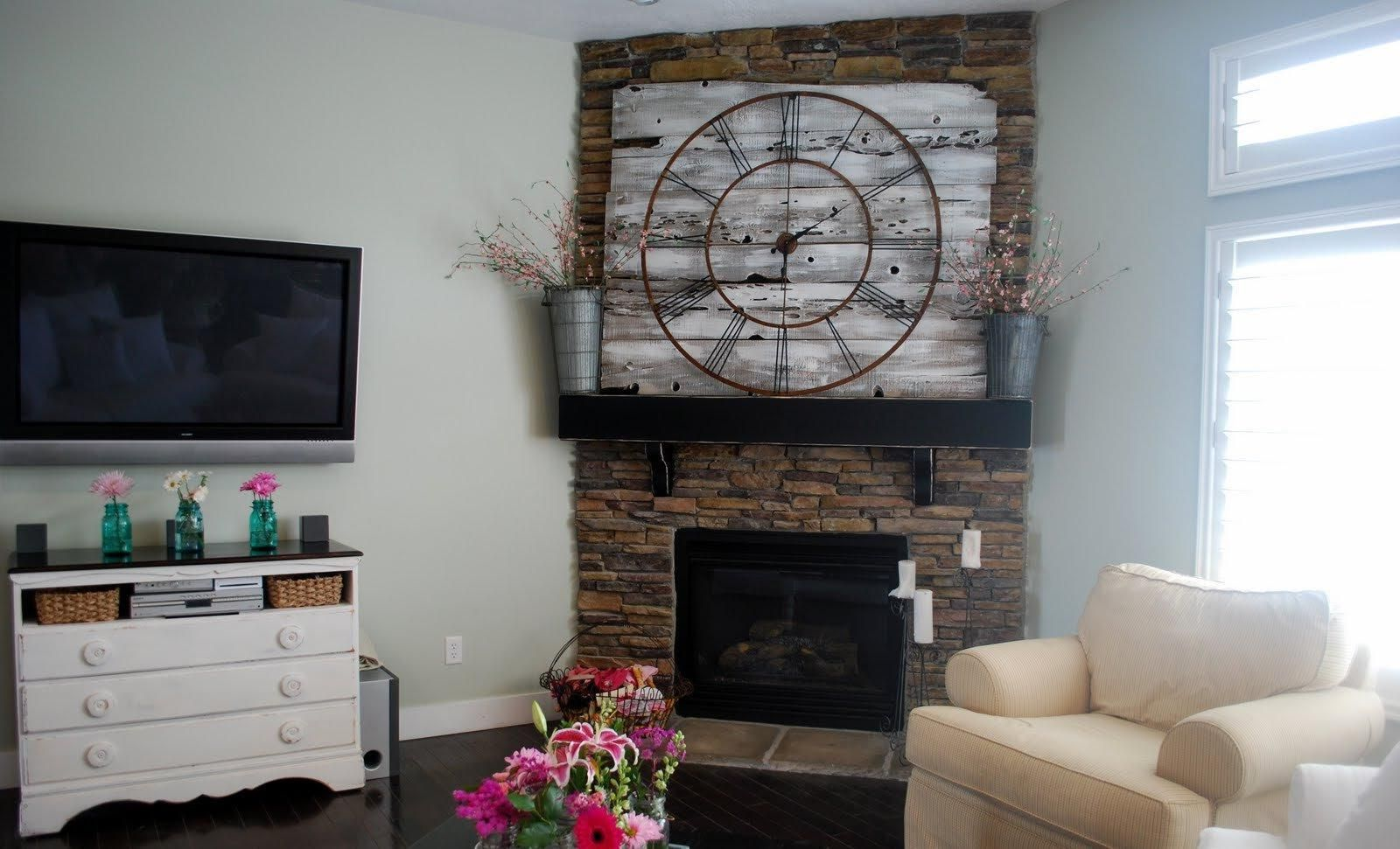 contemporary corner fireplace design with tv wall mount above white nightstand also beige chair beside glass wind0ow plus vintage clock above fireplace mantel