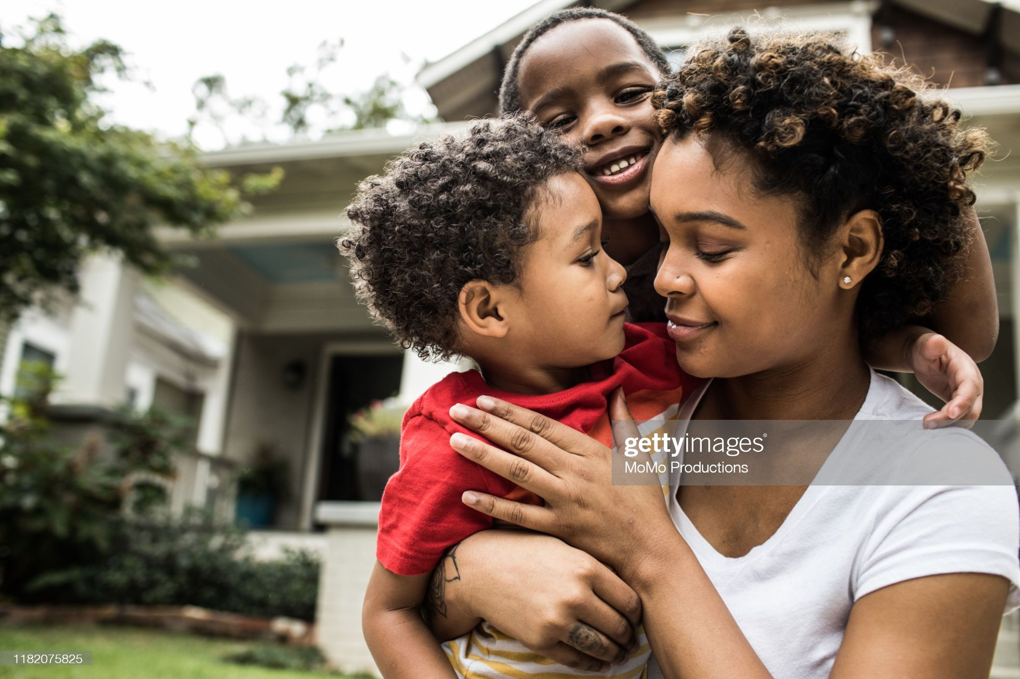 Single mother playing with young sons in front of house in