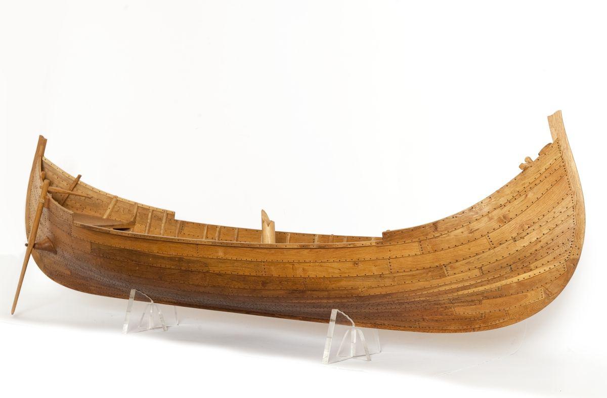 Fartygsmodell av ek, klinkbyggd på spant, högbordigt skepp (knarr) ÄSKEKÄRRSBÅTEN (fynd år 1933 fr. Göta älv, daterat 700 e. Kr.) Sidoroder på styrbordssidan, bordläggning förhöjd med ett bord i för- och akterskepp, liten back och halvdäck, kort kölsvin med mastspår.