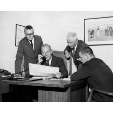 Four businessmen reviewing document in office Canvas Art - (24 x 36)