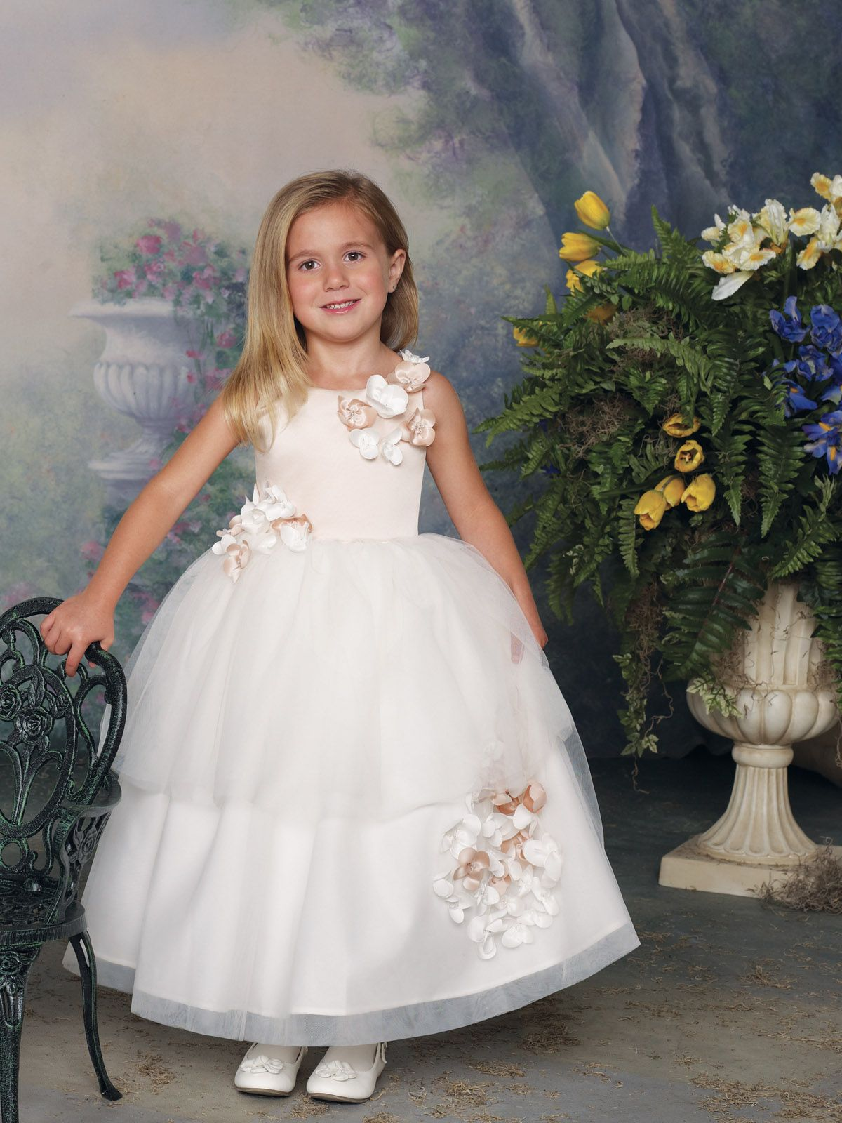 Sleeveless satin and tulle tea-length dress with jewel neckline, satin bodice accented with clusters of flowers, full dirndl double tiered tulle skirt features a matching cluster of flowers.Sizes: 2 - 16