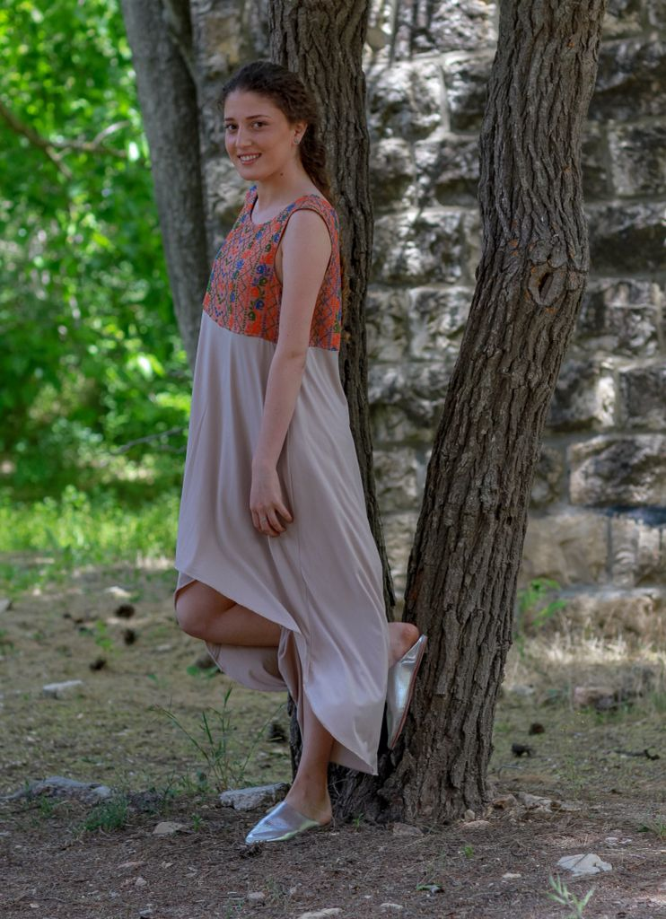 From Taita Leila's debut collection :The Qabbeh. Round collar with V back and asymmetrical length Yaffa dress. Hand-embroidered using cross-stitch with orange, blue and green threads, fabric is mesh and lycra Butterfly cut with loose fit. Available in peach/beige combination, casual or classy elegant spring/summer top fashion, can be worn with pants