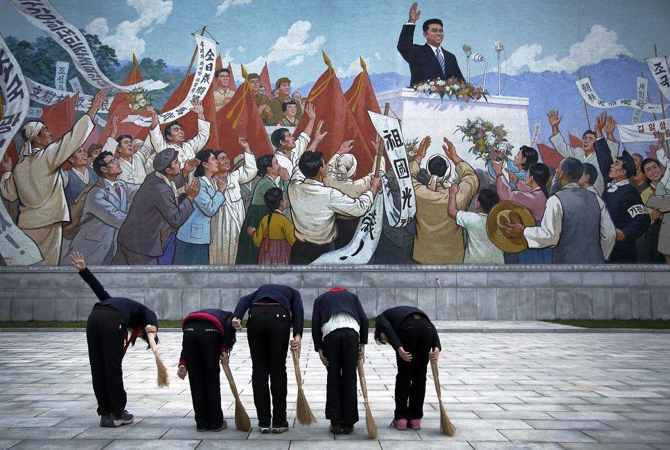 Delle bambine si inchinano davanti a un murales che raffigura Kim Il Sung durante un discorso. (AP Photo/Wong Maye-E)