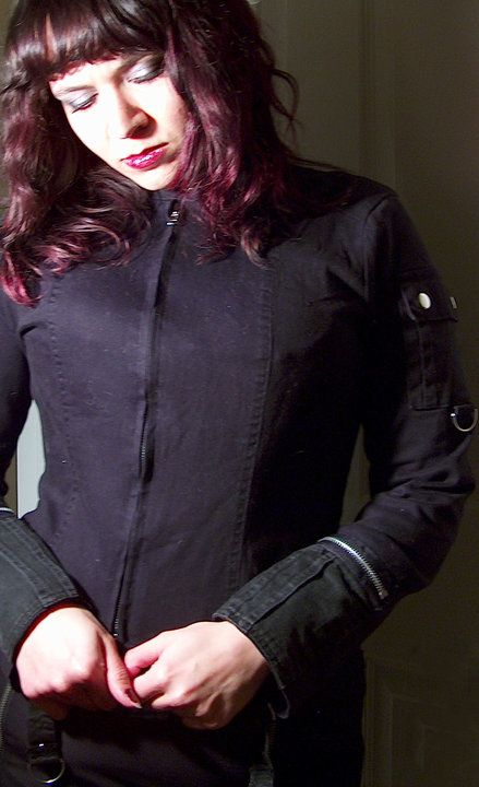 A few years ago, I customized this little black jacket from Forever 21, which I managed to score from a second-hand store for about $2. (I believe it is a Junior's Size Large.) I used materials from an old pair of Tripp Pants and a pair of laces from an old pair of Demonia Boots, which accented the color of the faded jacket, which I had pre-dyed with a violet/black cold dye. I added additional metal D-Rings and repaired the metal snaps that were on the shoulder pocket.