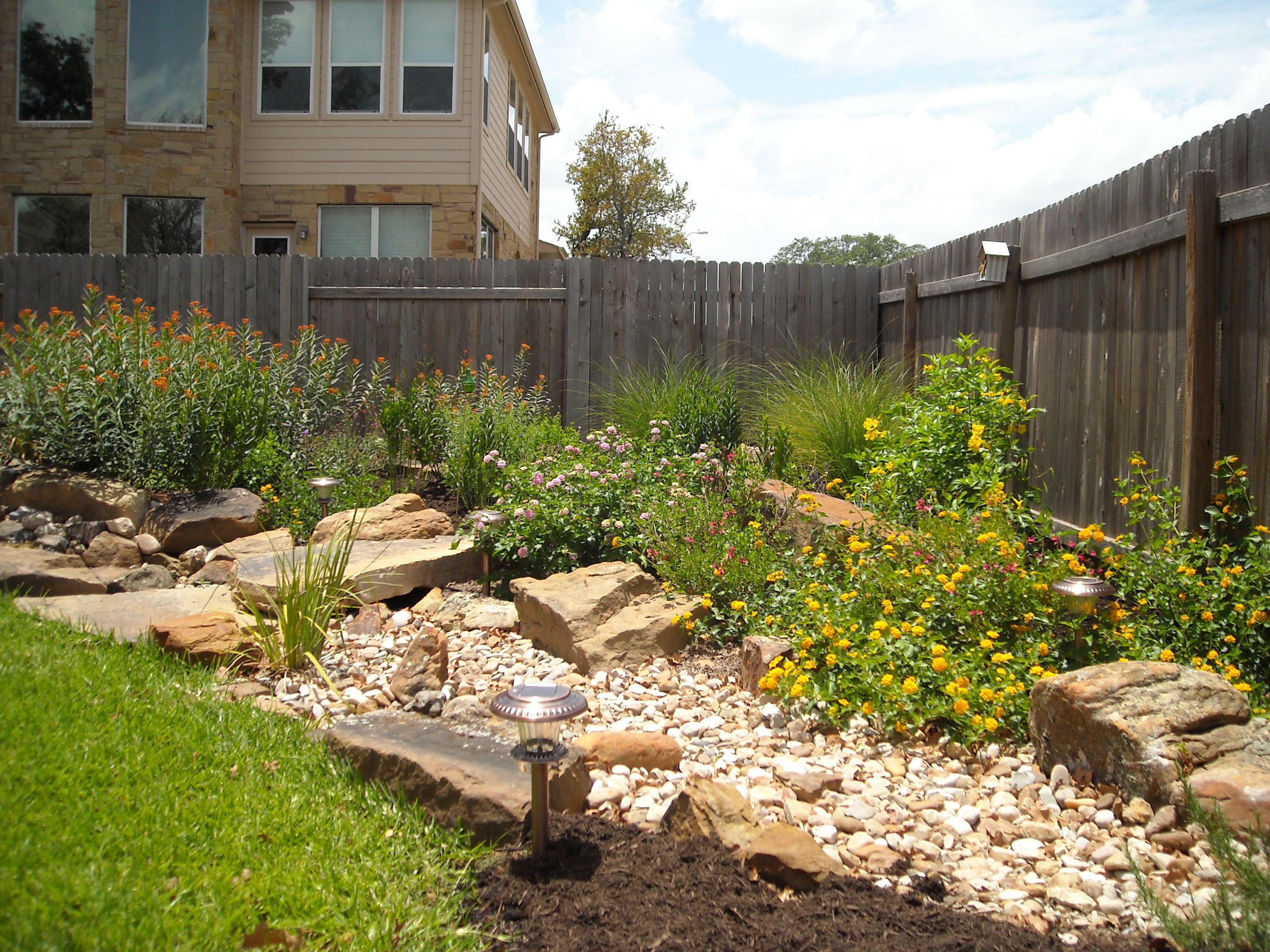 Water feature disappearing into a dry creek bed with a