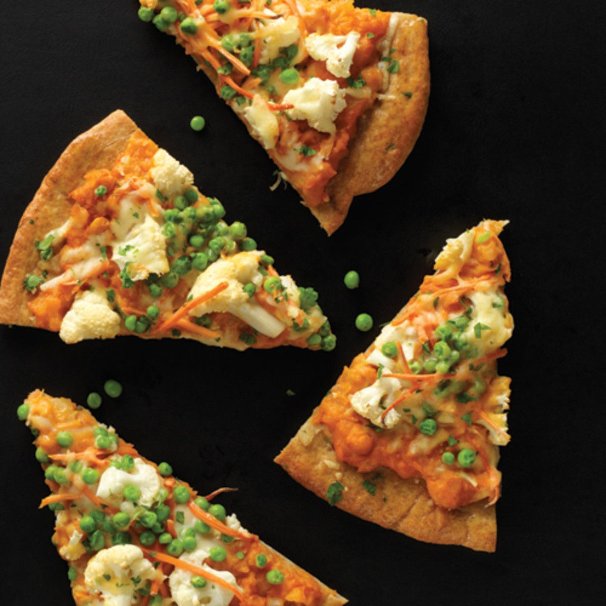 Coconut milk, curry paste, potatoes and chickpeas are simmered together to create the ultimate flavorful sauce in this scrumptious pizza. Colorful carrots, peas, cauliflower and cilantro leaves top it off for a vibrant, crowd pleasing meal.