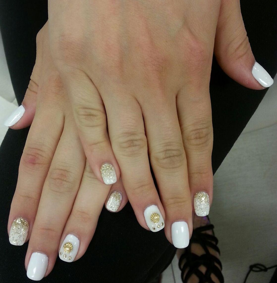 Gold shells and ombré gold glitter on white nails