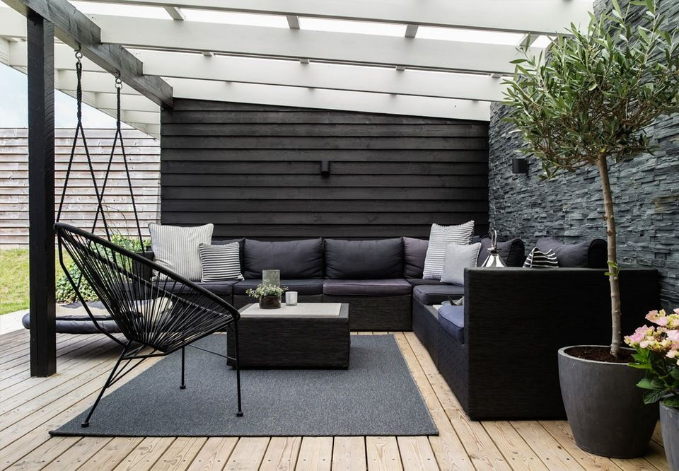 Lovely lounge area on the terrace with comfy and modern garden furniture and green plants.