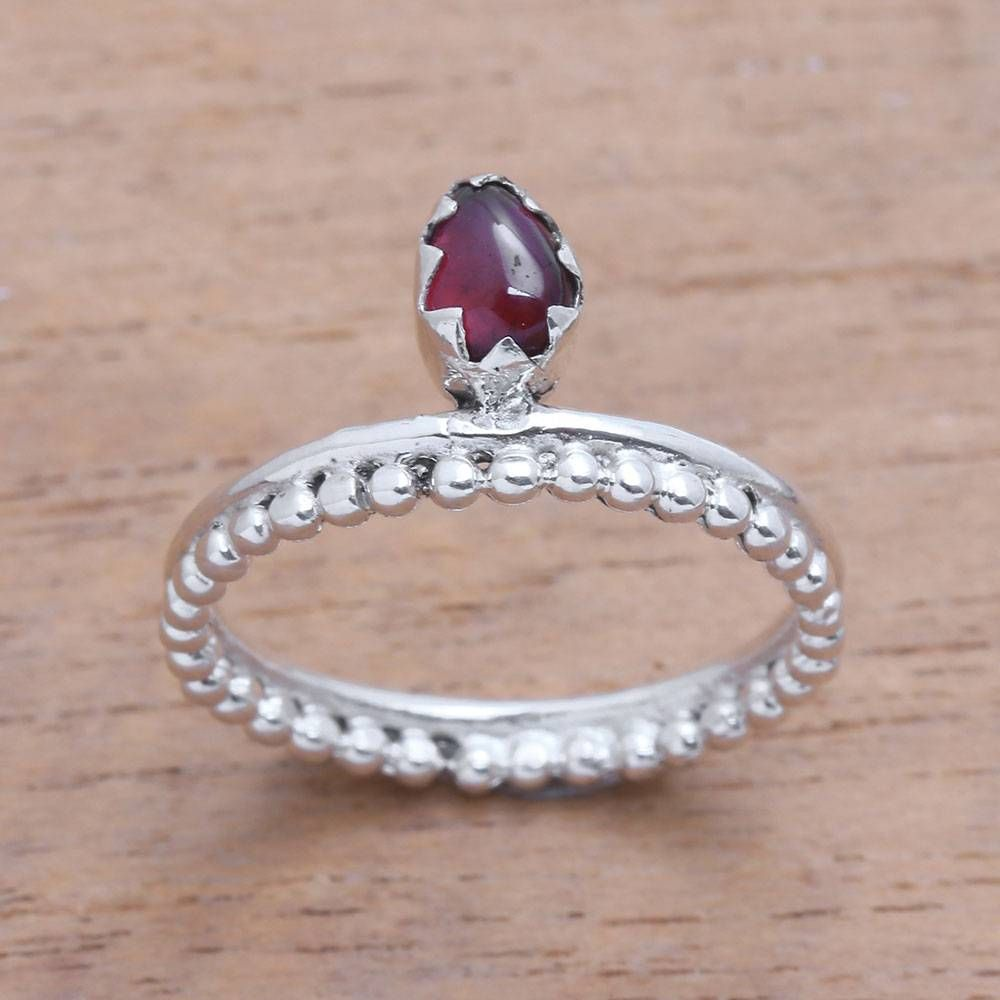 Possessing a serene beauty this lovely cocktail ring from Bali is designed by Ketut Sulastri. This ring circles the finger with a sterling silver band featuring handcrafted dot motifs. A cabochon of natural garnet is enshrined at the front.
