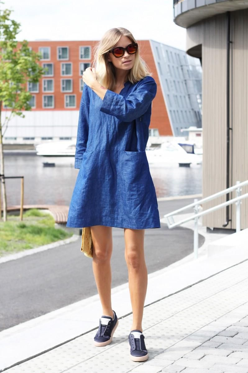 58e802835a5 How to Style a Denim Dress For Spring 2015 - long sleeve a-line blue denim  dress worn with sneakers and trendy cat-eye sunglasses