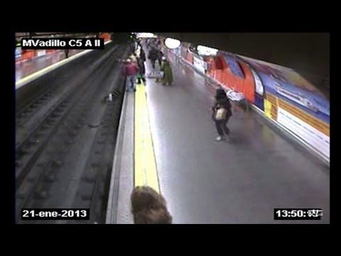 A Spanish policeman was Tuesday hailed a hero after a dramatic security video captured him rescuing a woman who fell onto the tracks of the Madrid metro moments before a train arrived. Duration: 00:56