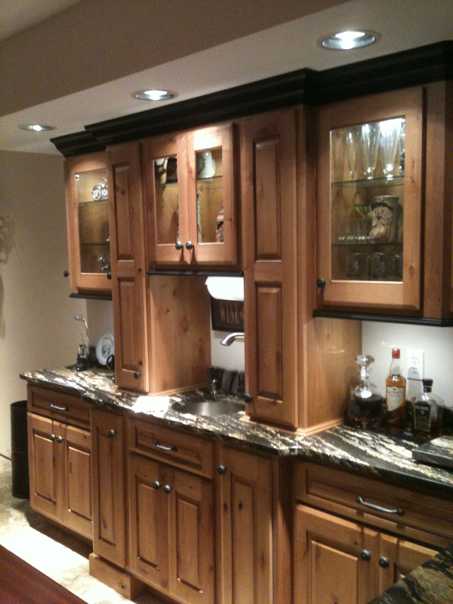 Knotty Alder Cabinetry Paint Black Crown Mold And Under Cabinet Mold This Is A Basement Bar Alder Kitchen Cabinets Wooden Kitchen Cabinets Cabinet Molding