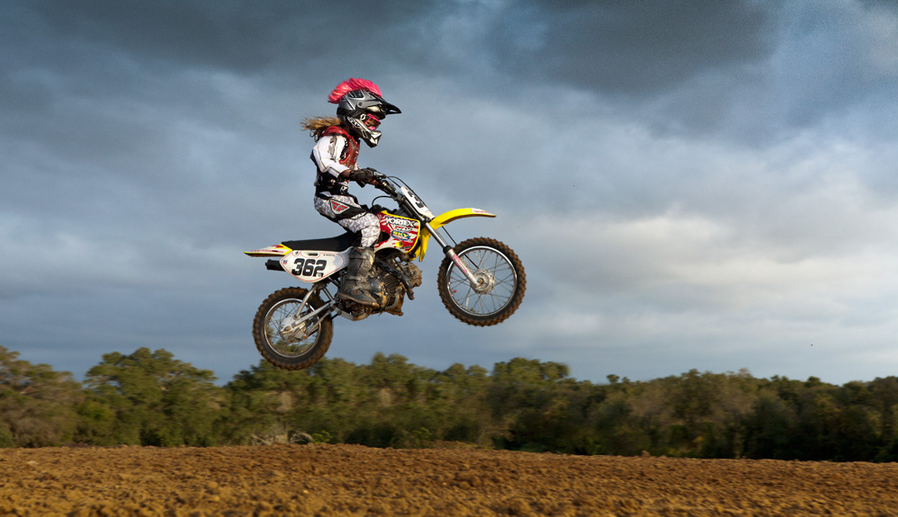 A Girl Jumping A Dirt Bike Awesome Clouds In The Background