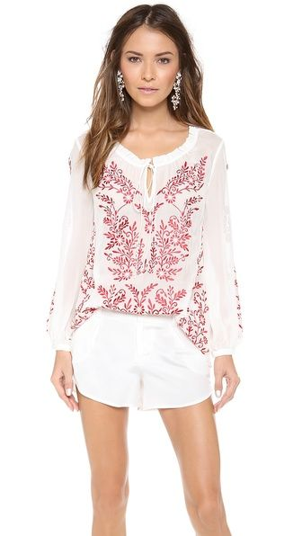 white peasant top tucked into white shorts with white floral/coral-esque earrings (alice + olivia Preston Embroidered Peasant Top, alice + olivia silk shorts, oscar de la renta enamel flower clip on earrings)