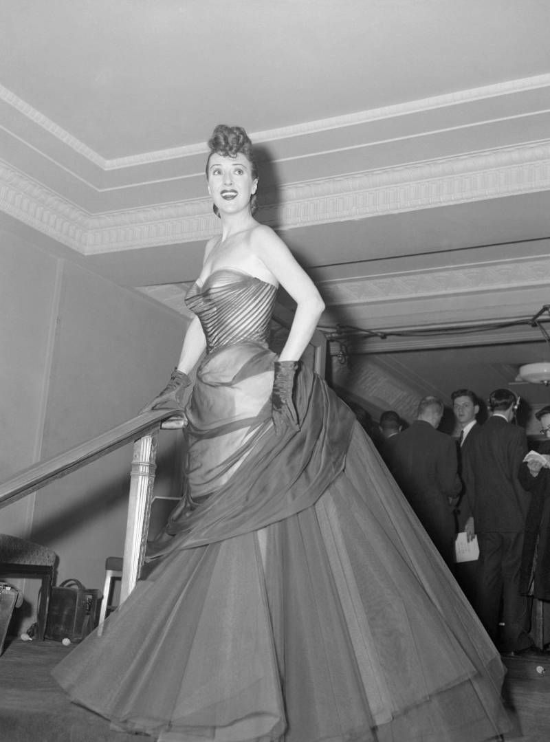 Gypsy Rose Lee wearing a Charles James gown in the March of Dimes annual fashion show, 1955.