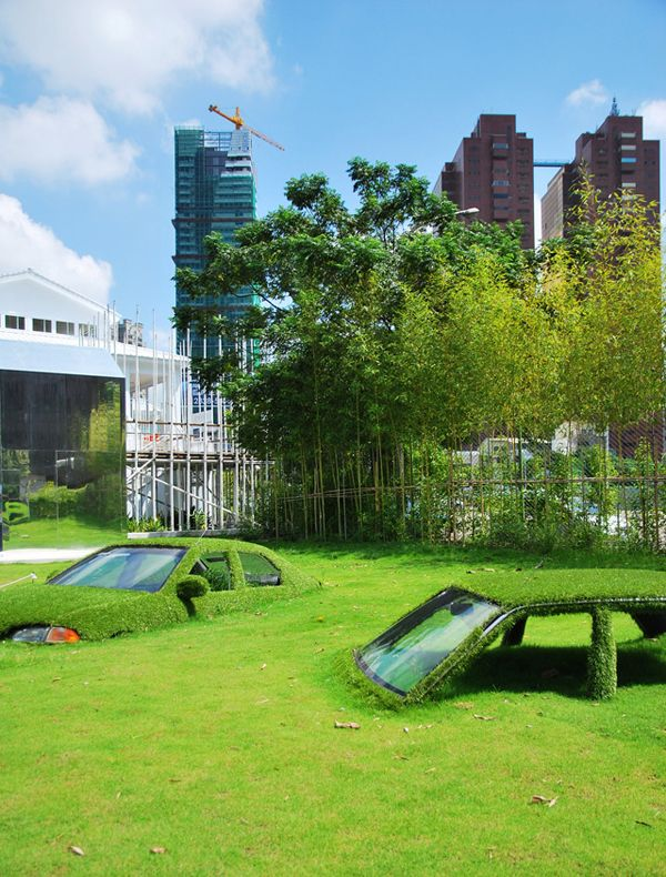 """""""In an effort to merge art, aesthetics, and nature, while promoting recycling, this installation features cars half buried underground at the CMP Block in Taiwan. The cars appear as if they are being pulled into the ground, and wrapped in grass, as if slowly becoming part of the earth."""" --enpundit, who notes that photos are by Toni Wang and Tao."""
