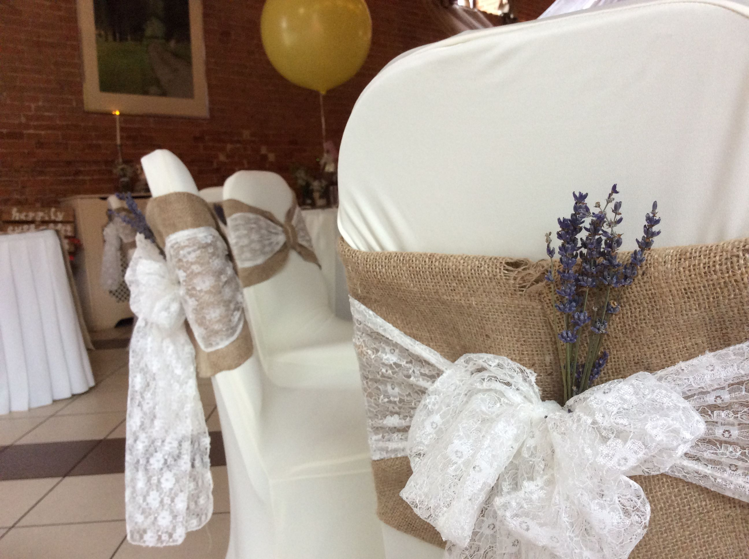 Rustic hessian chair covers with a delicate lace sash and a sprig