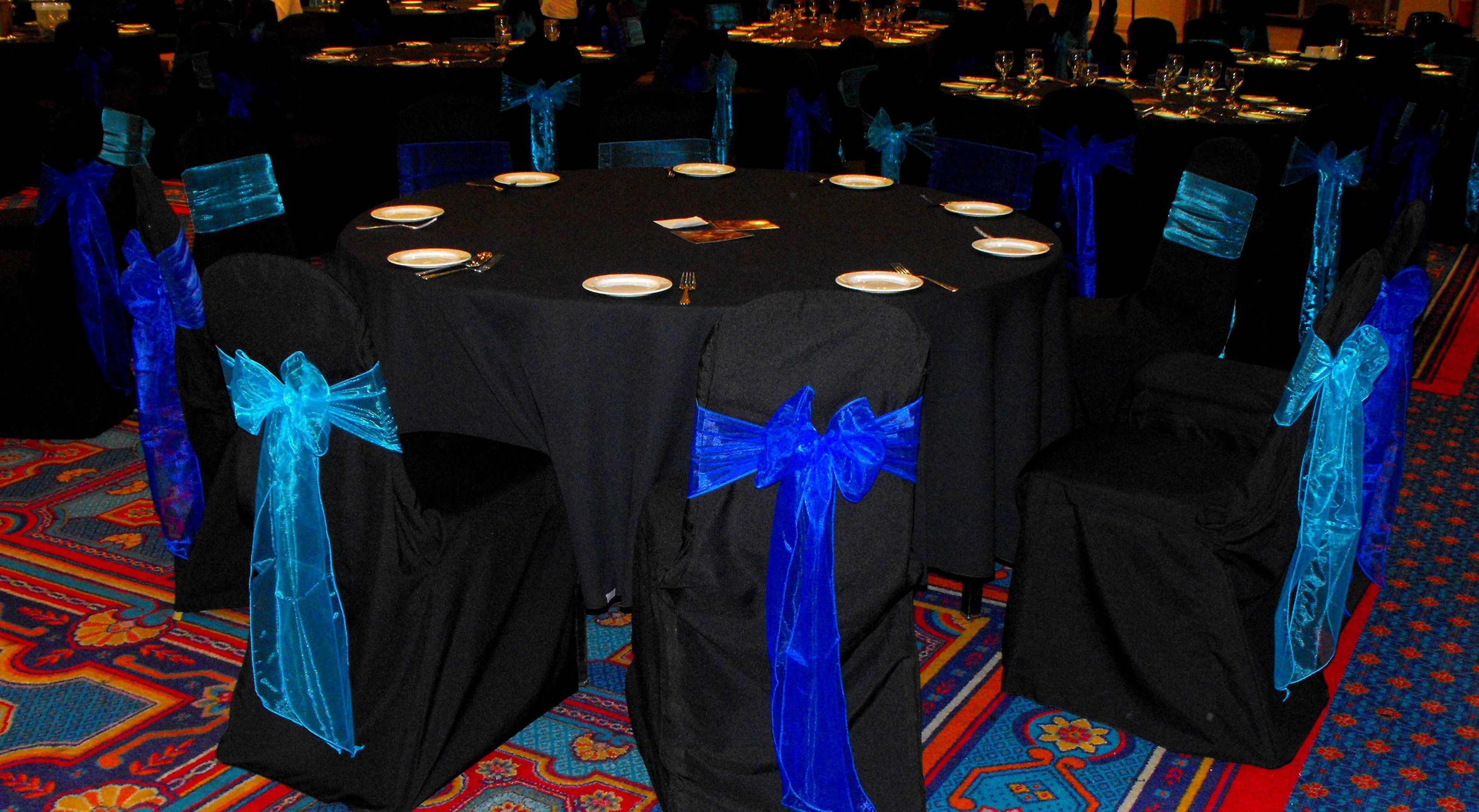 Alternating Turquoise and Royal Blue Organza on Black Chair Covers