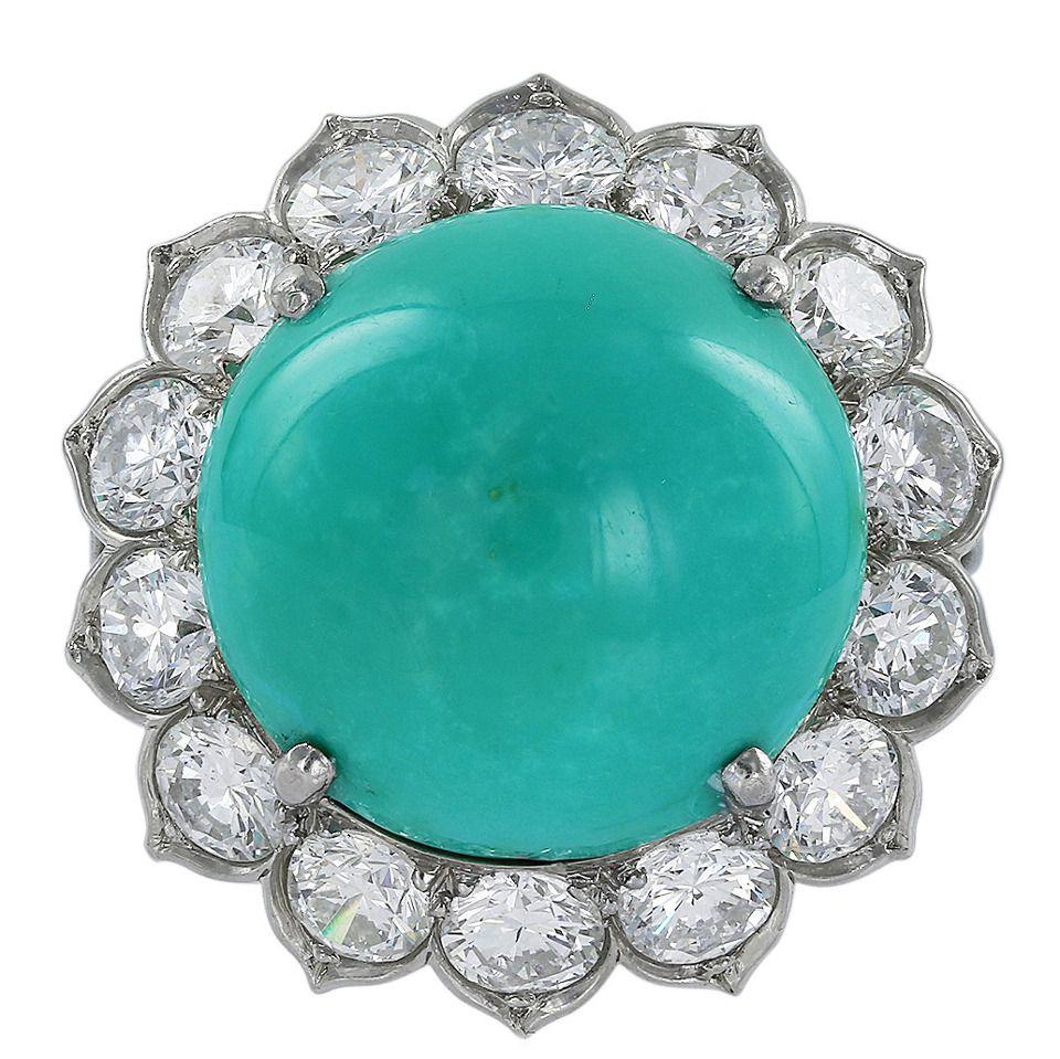 El platino anillo de racimo de la vendimia que consiste en el pedazo de turquesa cabujón mide aproximadamente 15.49 x 15.58 x 8.43mm rodeado de 1 fila que consta de 14 diamantes de corte redondo brillante con un peso total aproximado de 3,50 quilates de peso total. El anillo está firmado Van Cleef & Arpels,