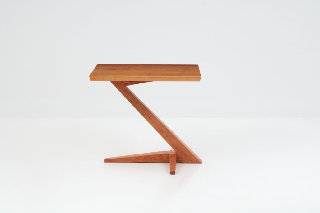 Edo Cantilever Side Table is part of Home Accessories Styling Side Tables - The Edo Cantilever Side Table challenges perception  Perched atop a solid cherry or walnut base that rises from its splayed foot on a dramaticallyangled leg, the table seems almost to defy the laws of physics   yet its ingenious design ensures its inherent stability  Designed with influences from Japanese, Danish and even Shaker styles, the table is a dramatic statement that accentuates its surroundings with grace