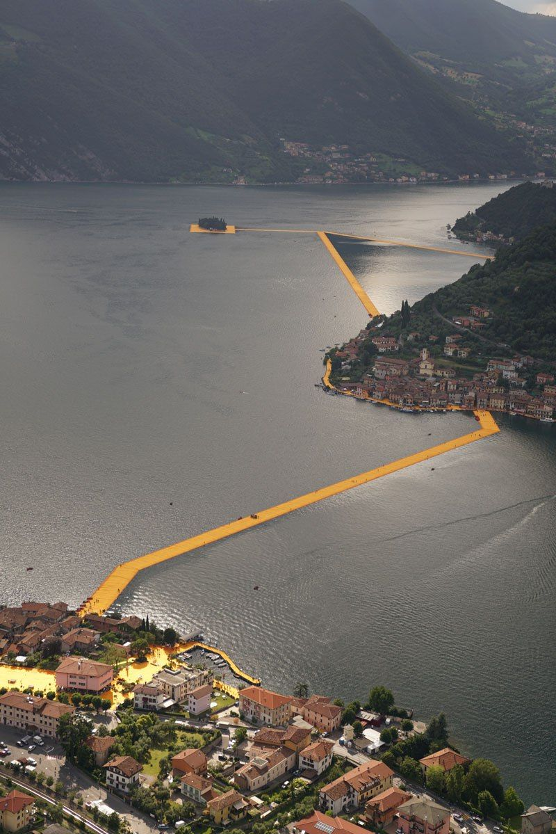 The Floating Piers is a temporary public art installation by artists Christo and Jeanne-Claude currently on display at Italy's Lake Iseo. From June 18 to July 3, 2016 (weather permitting), Lake Iseo will be reimagined. 70,000 square meters of shimmering yellow fabric, carried by a modular floating dock system of 200,000 high-density polyethylene cubes, will undulate with the movement of the waves as the Floating Piers rise just above the surface of the water.