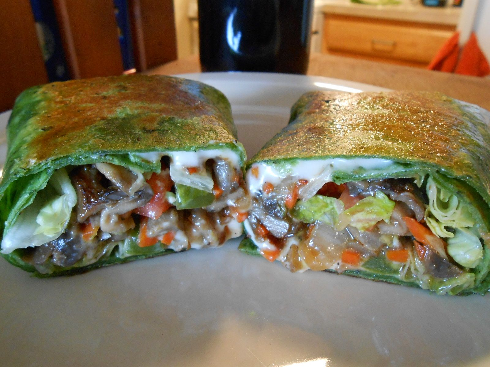 VEGGIE FAJITA WRAPS  Caramelized onion, mushrooms, peppers and carrot matchsticks wrapped in a spinach flour tortilla with dairy-free Swiss cheese, shredded lettuce and chopped tomato!  Makes 4 big ones