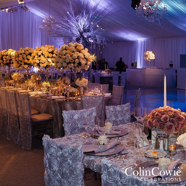 Blue and purple uplighting transforms this tented wedding reception.  #colincowie #CCCelebrations #CCSignature #lightingdesign #reception #weddingdecor #wedding #dancefloor #chandelier #centerpiece #tabledecor #whiteflowers #purple #silver via @angela4design