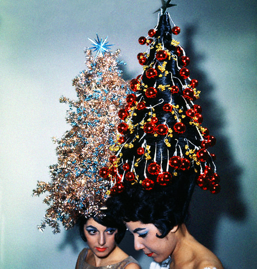 Two young women display their holiday hairdos, each with 42-inch hair decorated with tinsel and ornaments,1961.