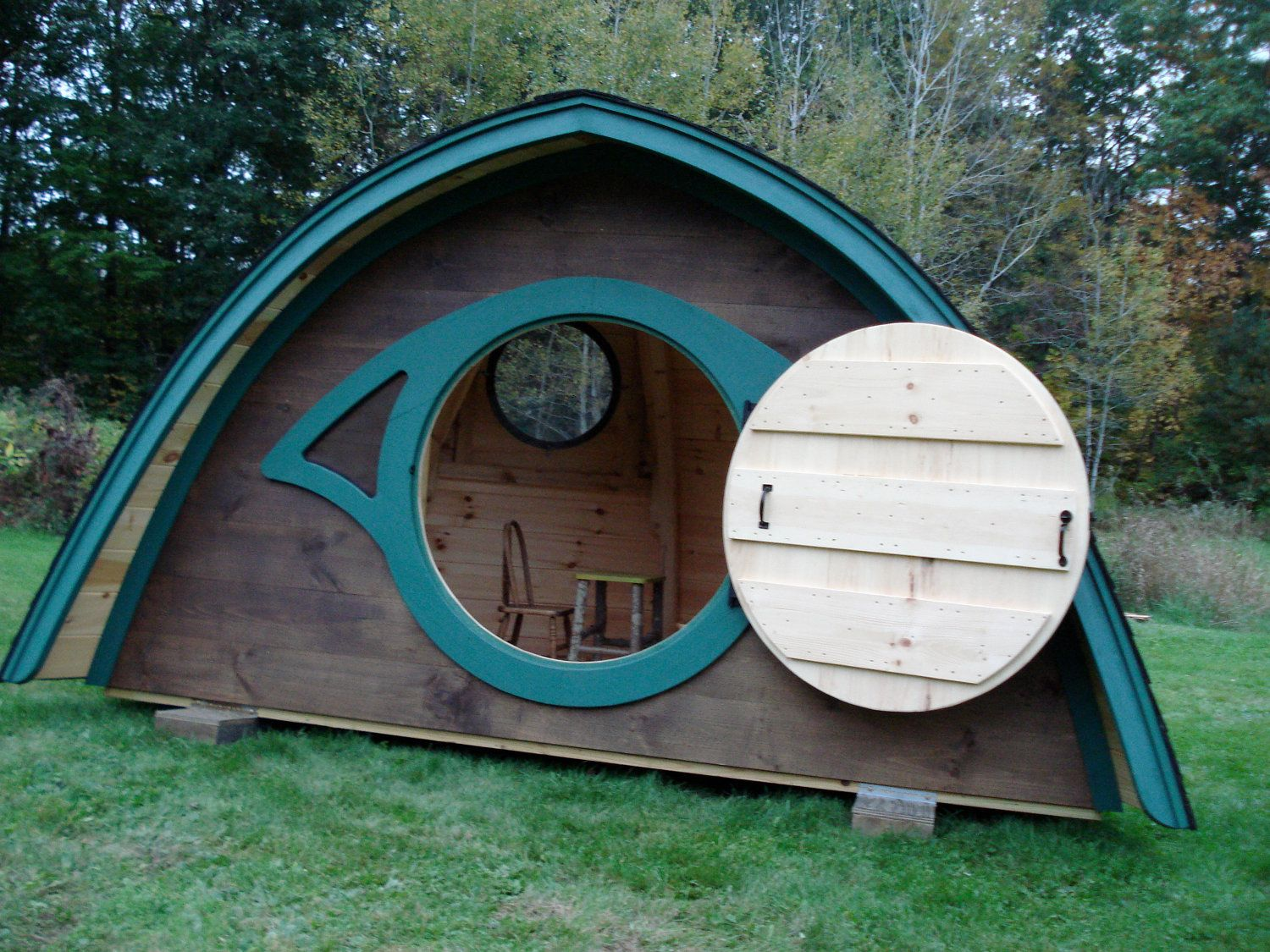 Attractive and spacious children's playhouse in the style of a Hobbit Hole, with a dome shaped front, curved walls, windows on either side of a round front door and a dormer with a round window. Provides a perfectly cozy enclosed space that kids will love to call their own.