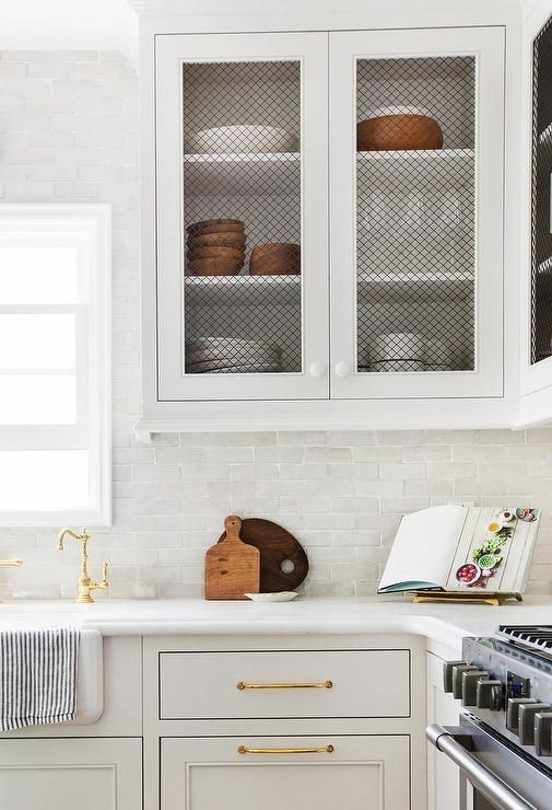 White kitchen features white cabinets accented with chicken wire ...