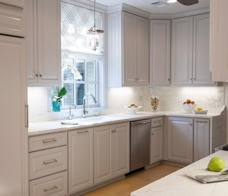 Beautiful Kitchen Features Light Gray Cabinets With Raised Panel Doors  Paired With Honed White Marble Countertops