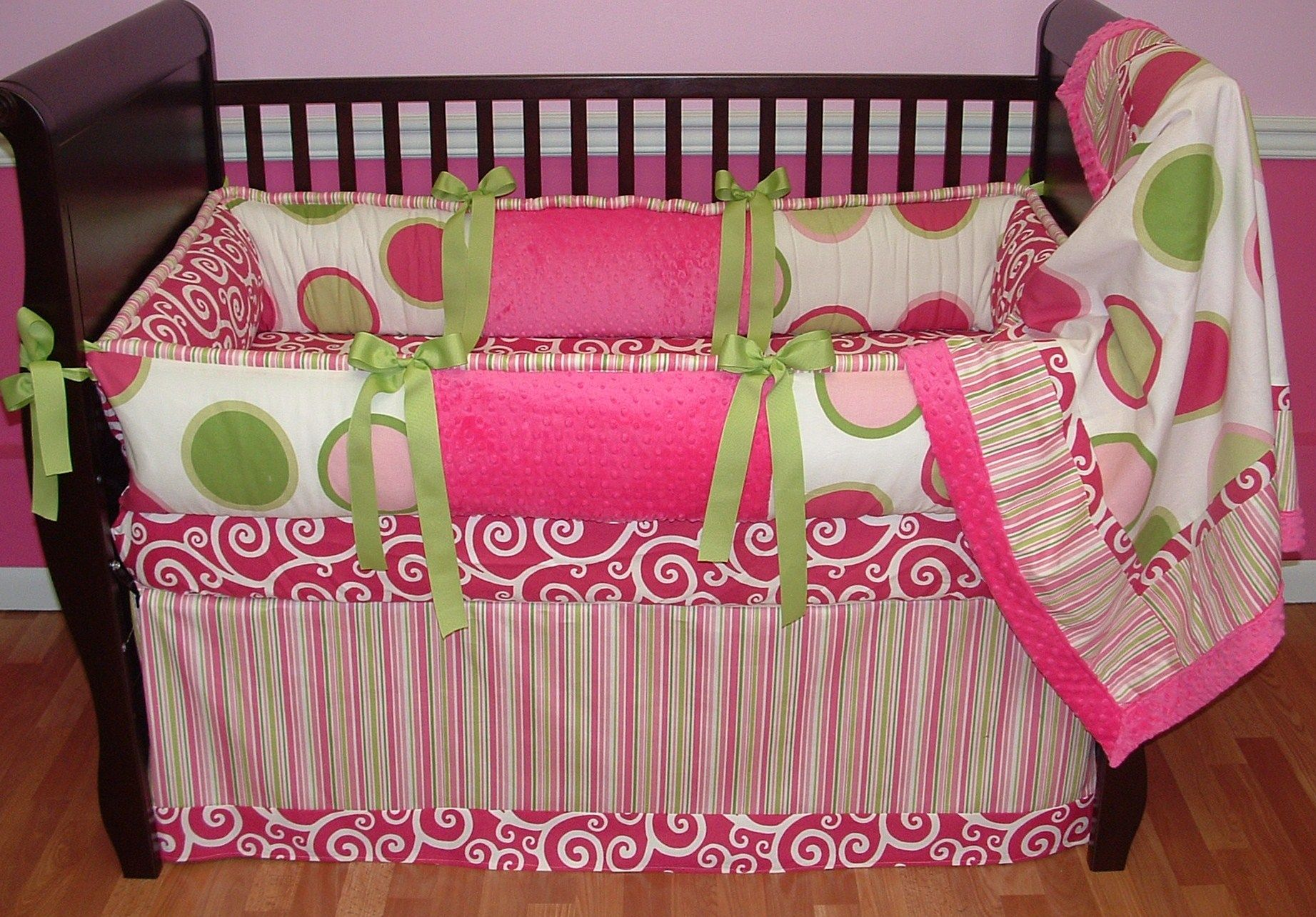 Pink Twister Crib Bedding   Included in this set is the bumper, blanket and crib skirt.  The stripe fabric is discontinued so your bedding will not come with a stripe. Some fabric rearranging will be made to  your bedding.