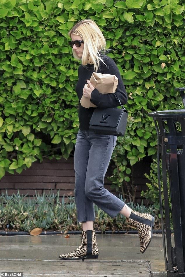 Emma Roberts looks stylish in a black sweater and statement boots