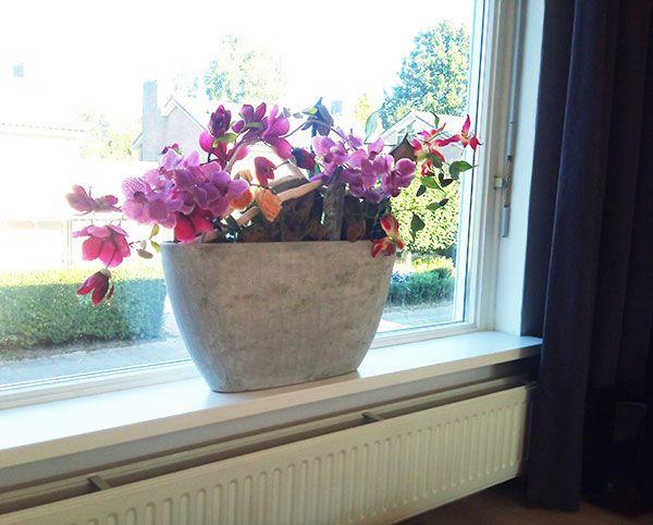 Decoratie met zijdebloemen en hout op de vensterbank in een ...