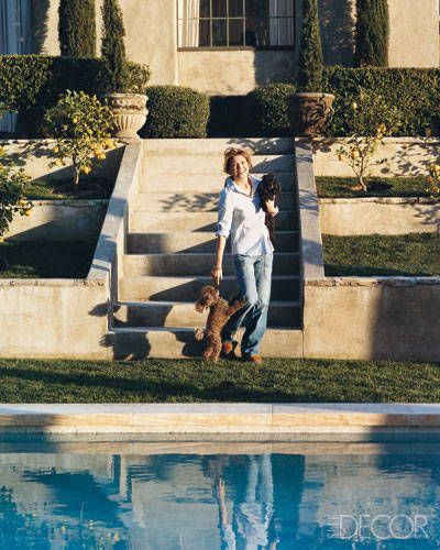 Ellen Pompeo plays with her toy poodles, Gigi and Valentino, beside the swimming pool at her home in the Hollywood Hills.   - ELLEDecor.com