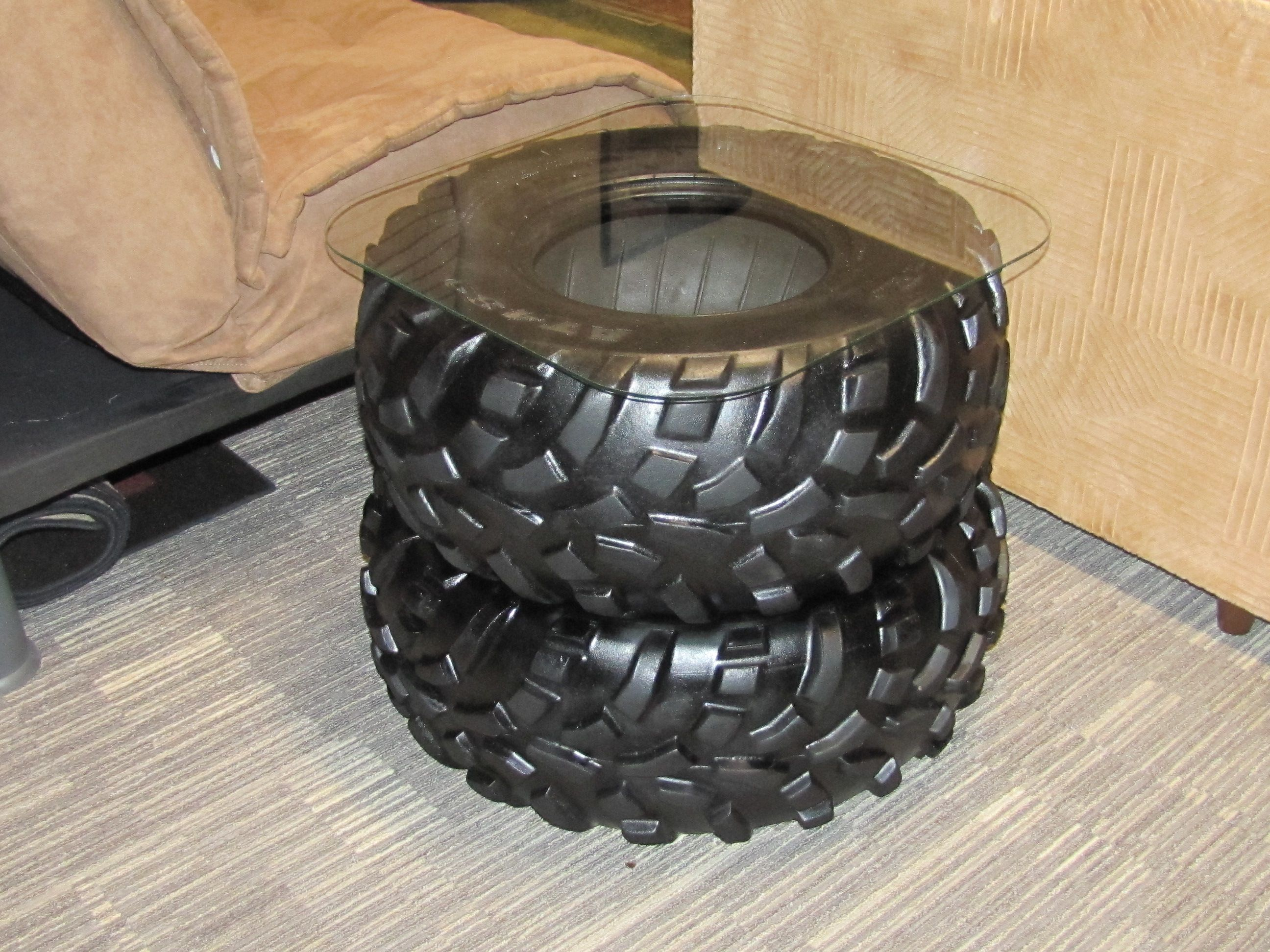 Recycled tractor tire coffee table in the waiting room at the tire man cave end table made out of 2 four wheeler tires and a glass top geotapseo Image collections