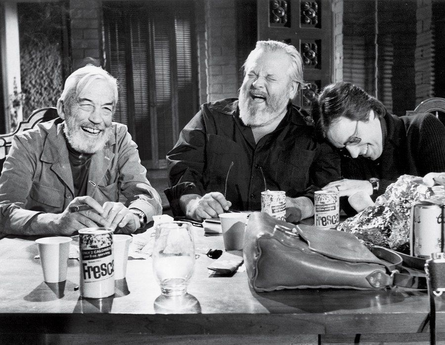 John Huston, Orson Welles, and Peter Bogdanovich take a break on the set of The Other Side of the Wind in the early 1970s.