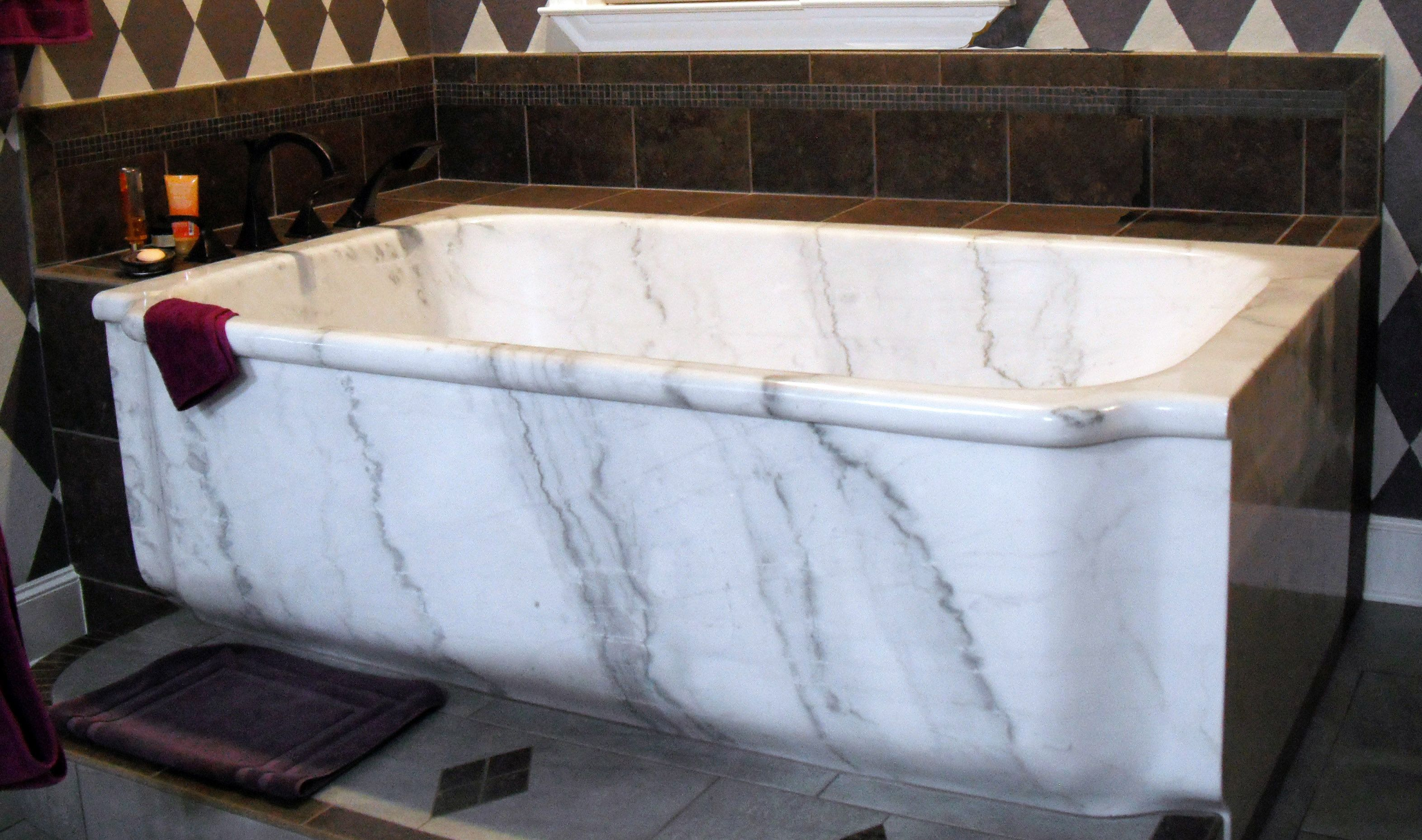 White marble bathtub in a bathroom corner. Square stone bathtub ...