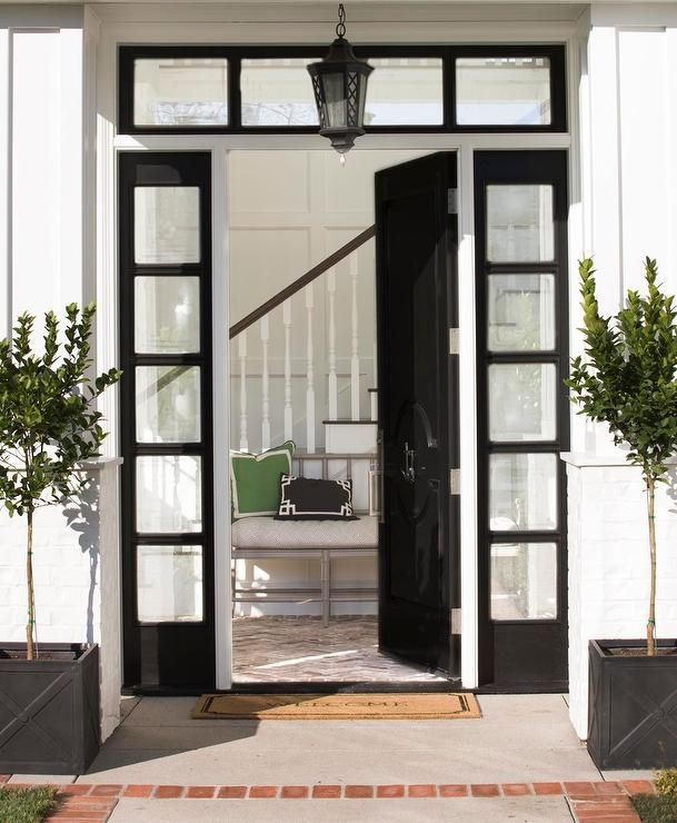 Superior Chic Home Features A Glossy Black Front Door With Black 5 Panel Sidelights  And Transom Window Illuminated By A Black Lantern Flanked By Potted Plants  In ...