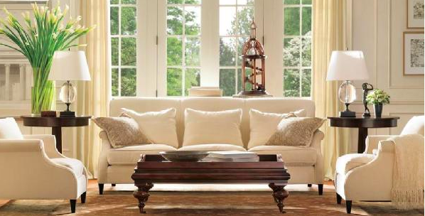 soft white seating.  white walls.  green plants.  dark wood furniture to contrast.  lamps.