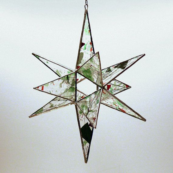 "Fantasy Star by colorandlight on Etsy, $44.00. This 12-pointed star is made from textured clear glass with ""fractures and streamers,"" red and green chips of glass and filaments of green glass in varying lengths and shapes, each more delicate than a blade of grass. This fantasy in stained glass is approximately 11 inches tall and 9 inches across. Chain for hanging your star is included."