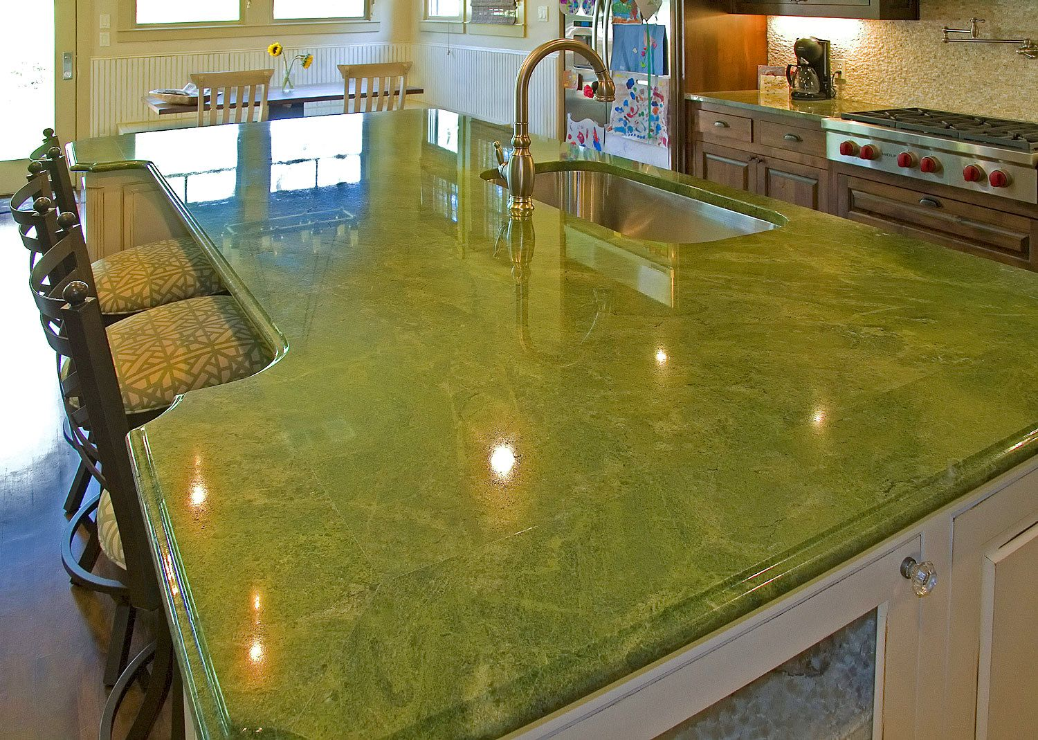 Unusual granite countertops color in solid green with grains and installed on white island and brown wood cabinets