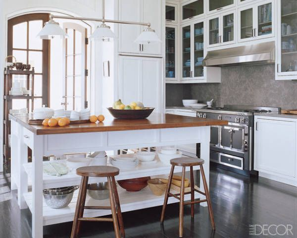 White always looks great with dark wood. We love the chic rustic vibe of this Florida kitchen, decorated by Robert Couturier and topped by a three-light chandelier by Ann-Morris antiques. See more designer kitchen islands. William Waldron  - ELLEDecor.com