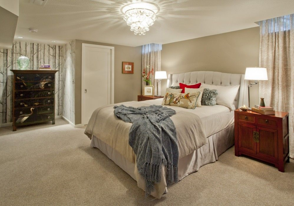 A beige room gets some much-needed flair with red and blue accents and a shining chandelier.
