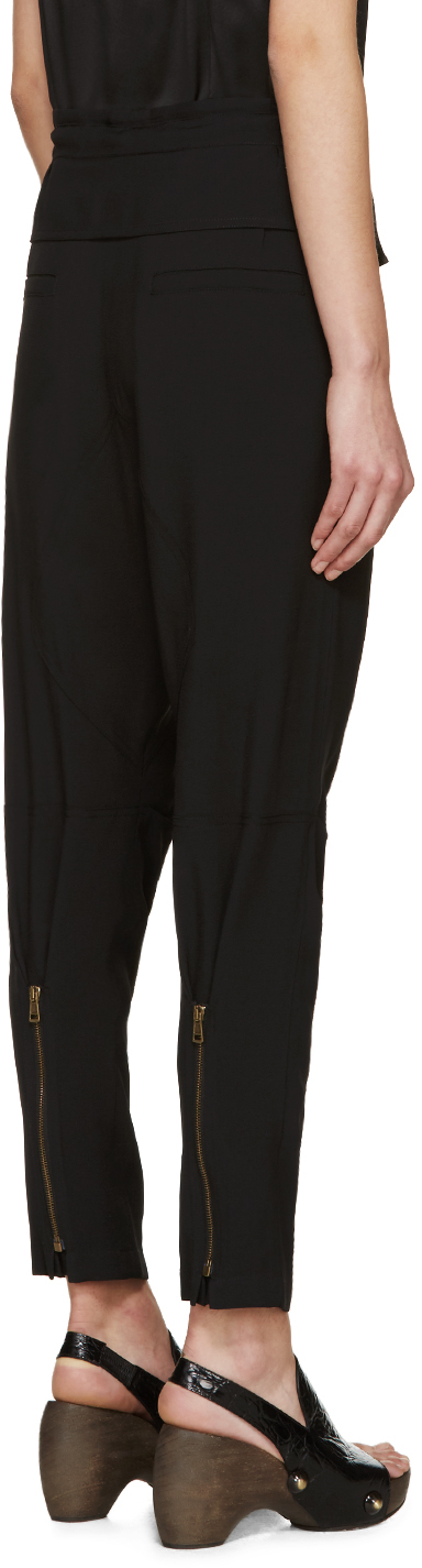 Slim-fit crepe sarouel-style trousers in black. Drawstring and overlay panelling at waistband. Four-pocket styling. Dropped inseam. Pleats at knees. Zippered expansion panel at cuffs. Unlined. Brass-tone hardware. Tonal stitching.