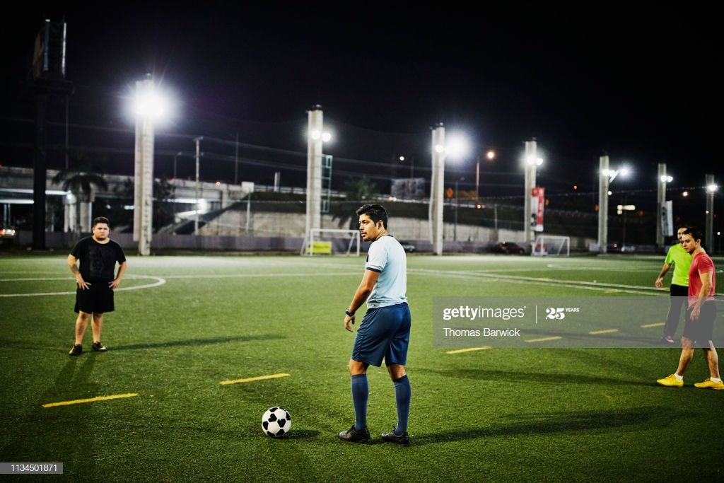 Male soccer player preparing to kick ball during evening
