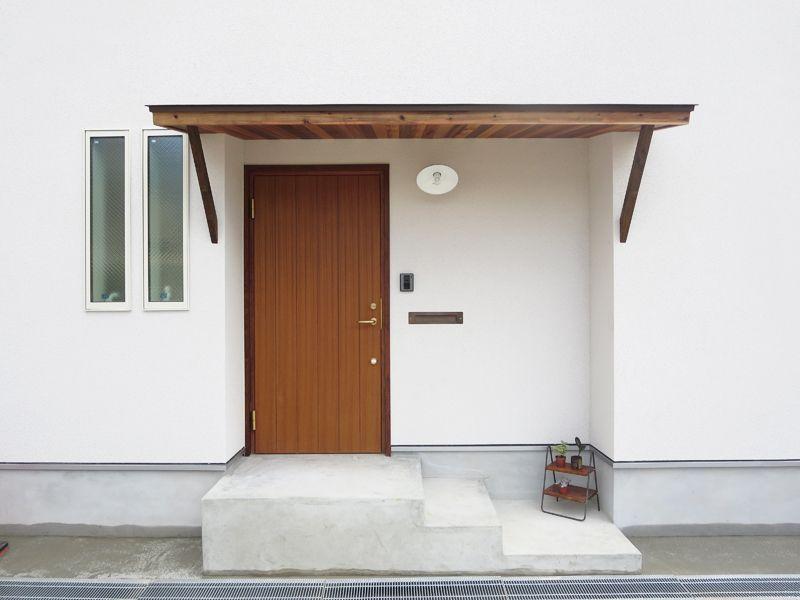 木製ドアと 庇が真っ白な外壁のアクセントに 家 玄関庇 庇